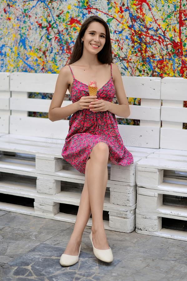 Dziewczyna z lody w jej rękach siedzi na tle jaskrawy zdjęcia royalty free