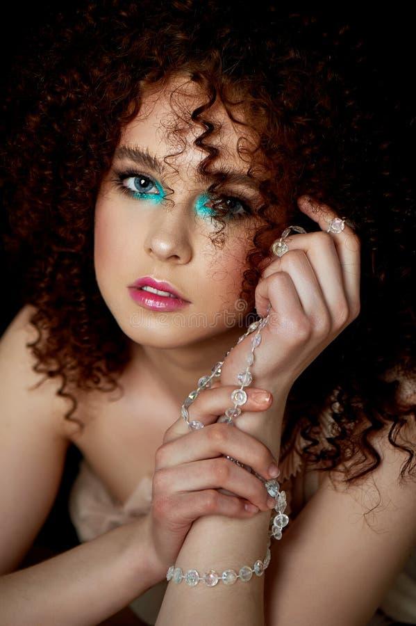 Dziewczyna z luksusowym kędzierzawym czerwonym włosy Delikatny makeup z sztucznymi rzęsami w lala stylu Na patroszonych nicianych zdjęcie royalty free