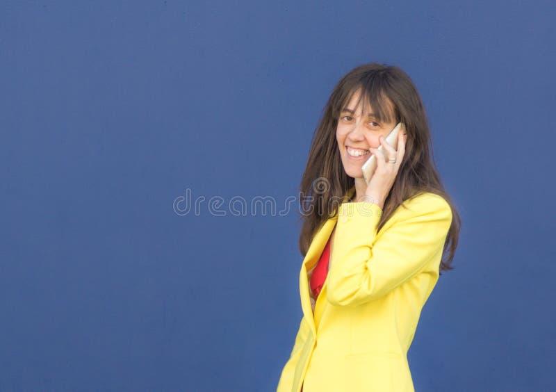 Dziewczyna z mobilną patrzeje kamerą obraz stock