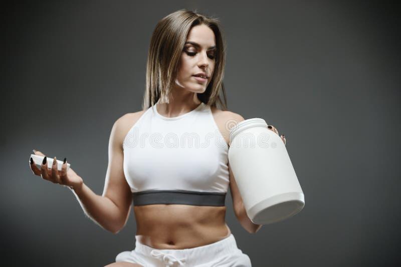 Dziewczyna z nadprogram serwatki potrząśnięcia proteinowym proszkiem obraz stock