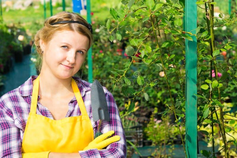 Dziewczyna z narzędziem dbać dla rośliien w ogródzie obraz stock