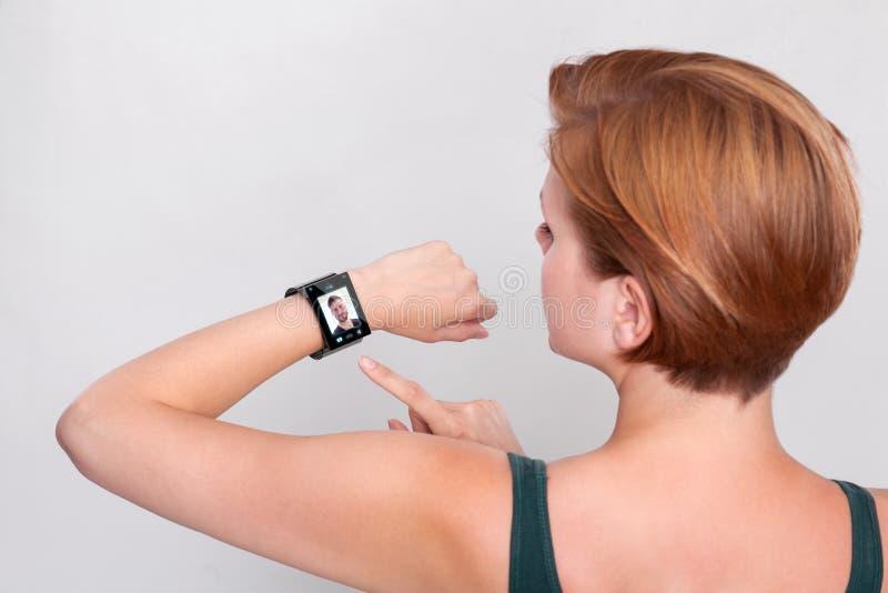 Dziewczyna z nowożytnym Internetowym Mądrze zegarkiem na popielatym tle obraz stock