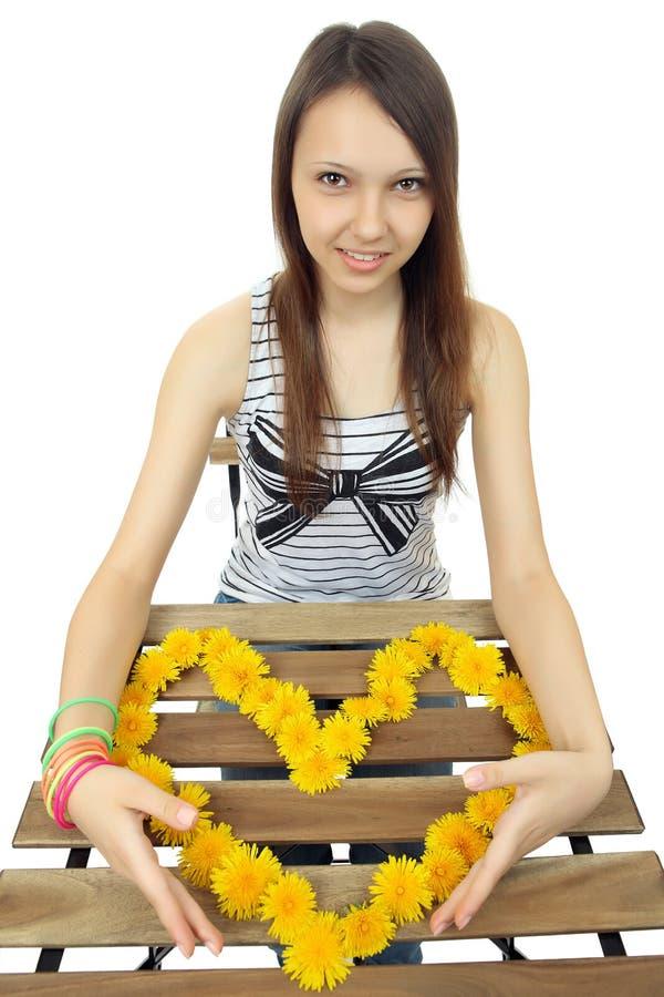 Dziewczyna z ogromnym sercem, komponującym żółty dandelion kwitnie. zdjęcie stock