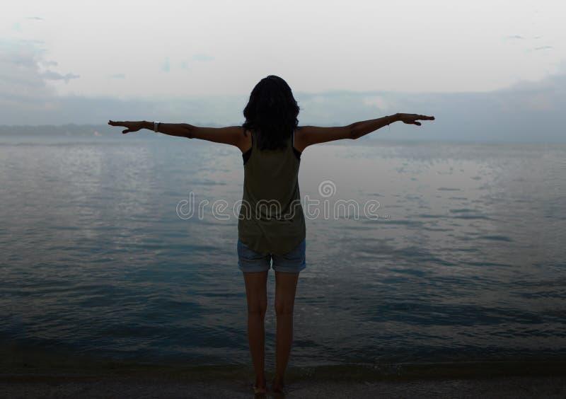 Dziewczyna Z Otwartymi rękami robi Latającemu gestowi na plaży obraz stock