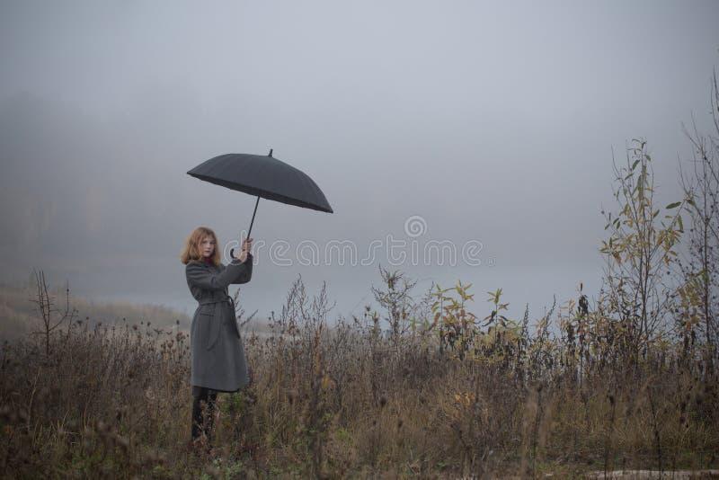 Dziewczyna z parasolem w jesieni polu zdjęcie stock