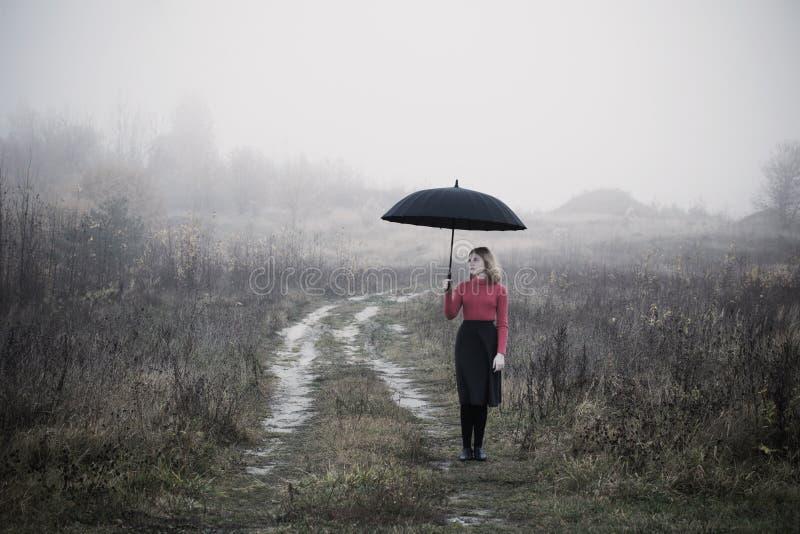 Dziewczyna z parasolem w jesieni polu fotografia royalty free
