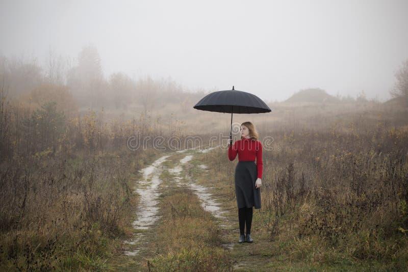 Dziewczyna z parasolem w jesieni polu zdjęcia stock