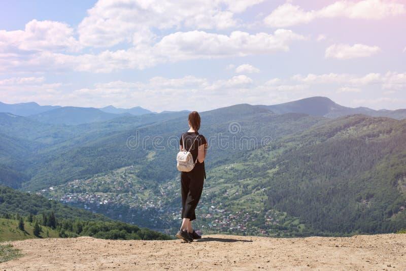 Dziewczyna z plecak pozycją na wzgórzu i podziwiać widok zdjęcia royalty free