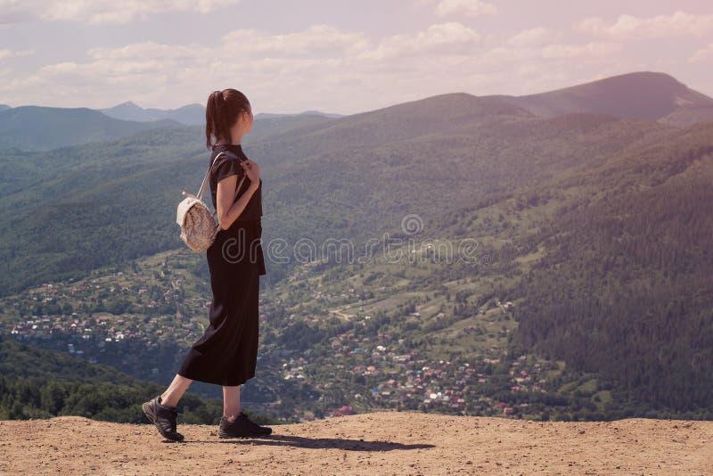 Dziewczyna z plecak pozycją na wzgórzu i podziwiać widok zdjęcia stock