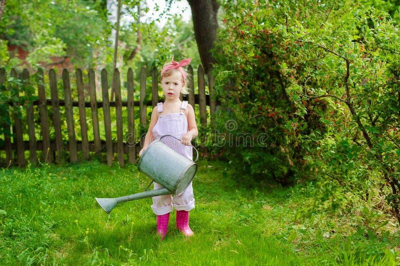Dziewczyna z podlewanie puszką w ogródzie obraz royalty free