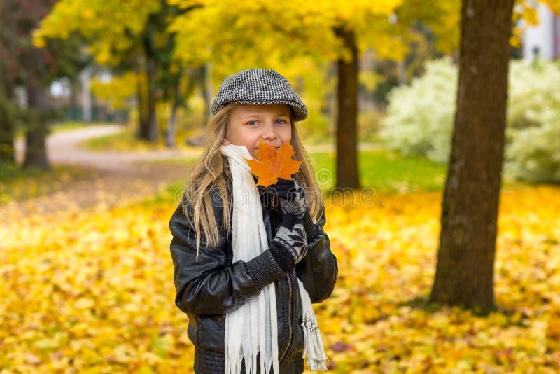 Dziewczyna z pomarańczowym liściem w jesień parku zdjęcia stock