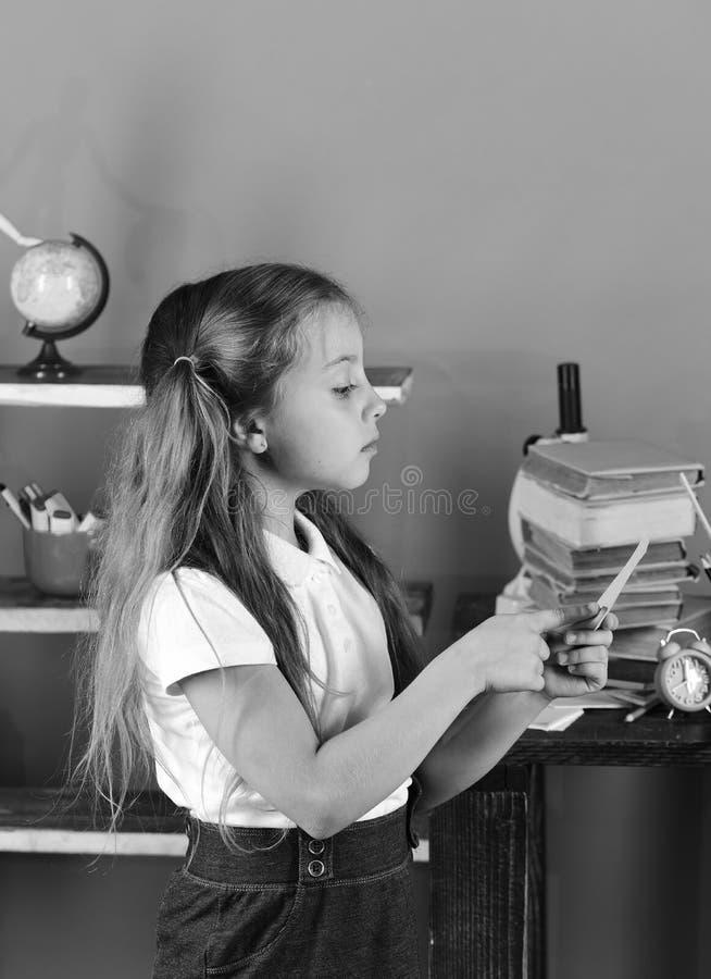Dziewczyna z ponytails stojakami stosem książki i półka na książki Uczennica z dumnych twarz chwytów różowym kawałkiem papieru zdjęcia stock