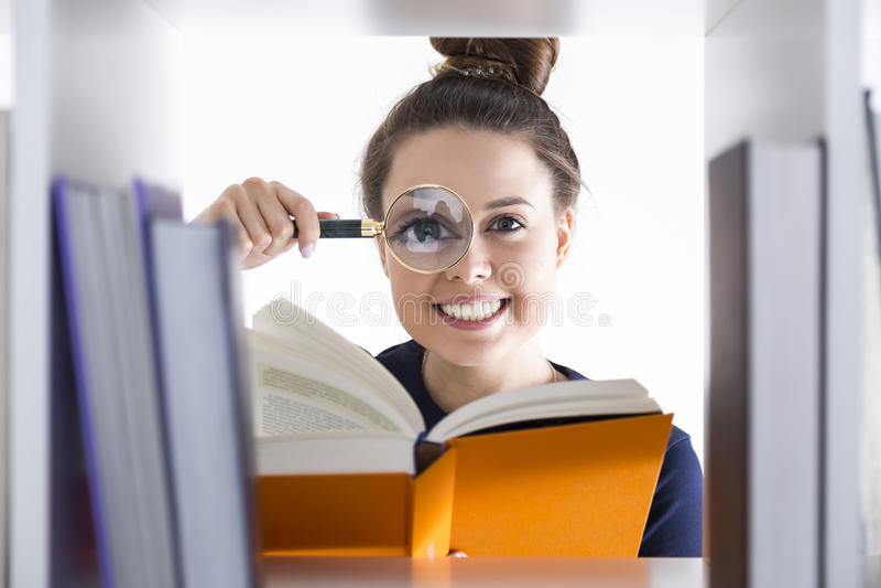Dziewczyna z powiększać - szkło, biblioteka zdjęcie stock