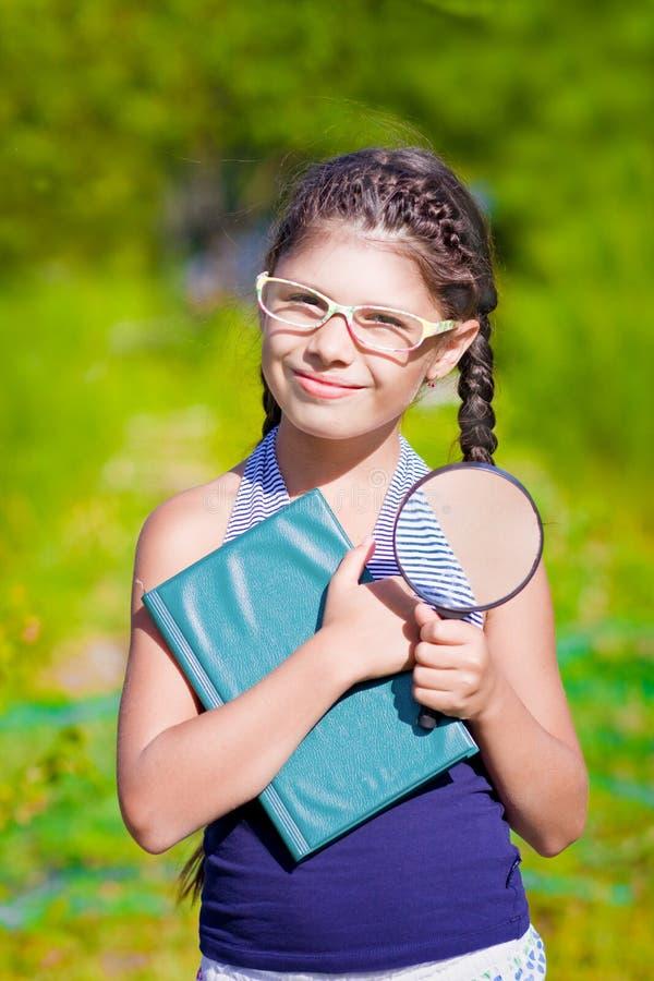 Dziewczyna z powiększać - szkło i książka zdjęcie stock