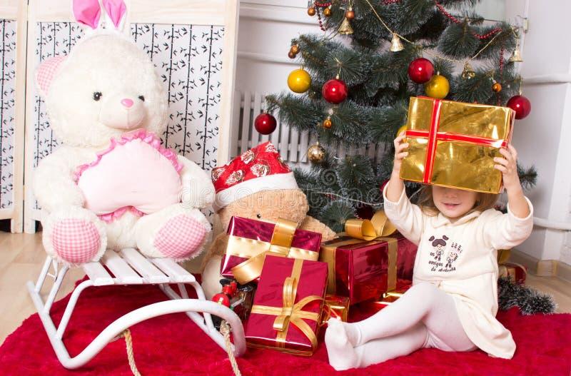 Dziewczyna z prezentami pod jedliną zdjęcie royalty free