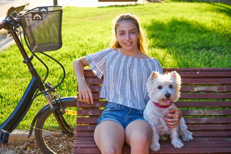 Dziewczyna z psim obsiadaniem w parkowej ławce zdjęcia royalty free