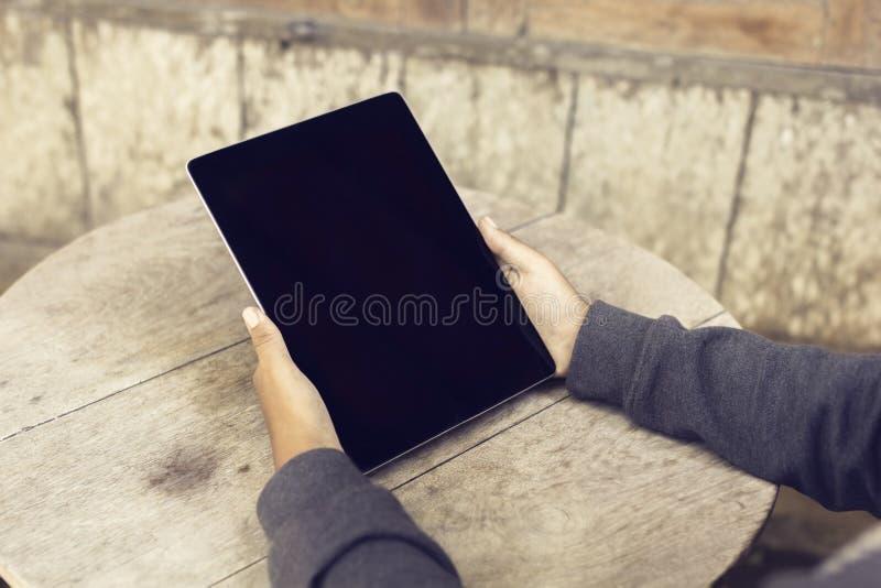 Dziewczyna z pustym cyfrowym pastylka ekranem i drewniany stołowy plenerowym obraz stock