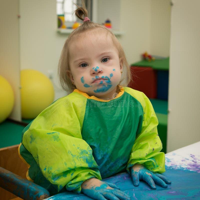 Dziewczyna z puszka syndromem zakrywającym w farbie gdy rysujący fotografia royalty free