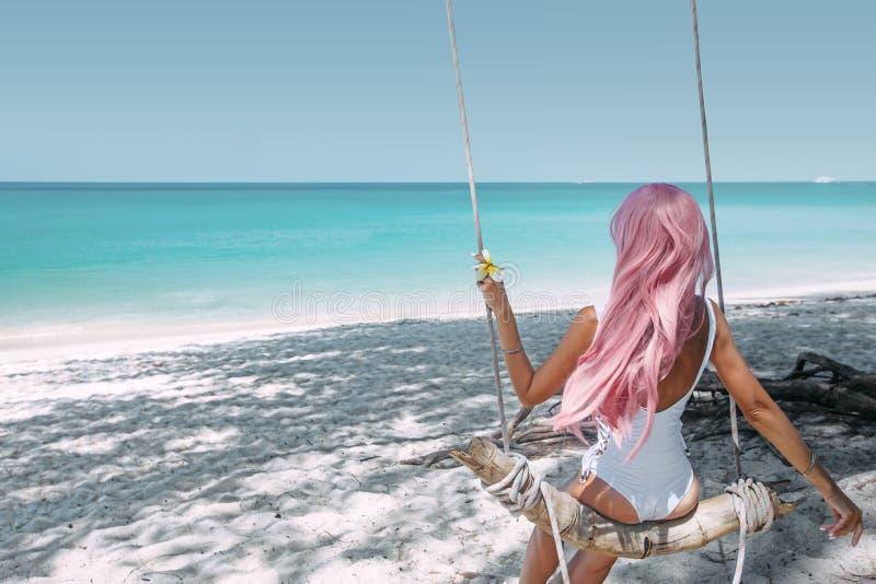 Dziewczyna z różowym włosianym obwieszeniem na huśtawce przy plażą zdjęcie royalty free