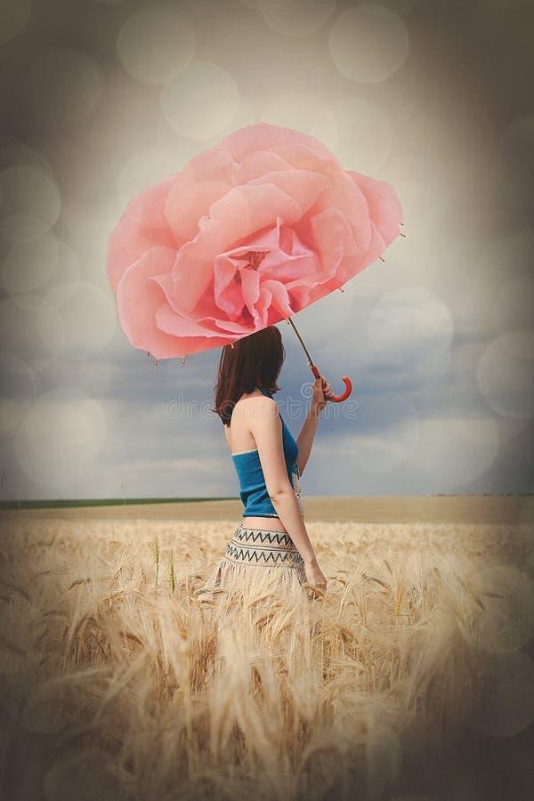 Dziewczyna z różanym parasolem przy polem w deszczowym dniu zdjęcia royalty free