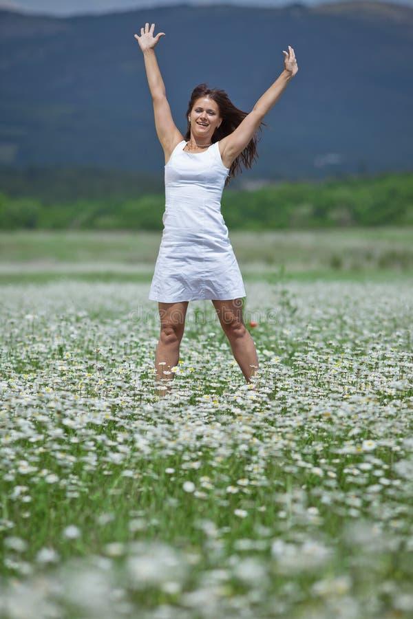Dziewczyna z rękami podnosić w chamomile polu zdjęcie royalty free