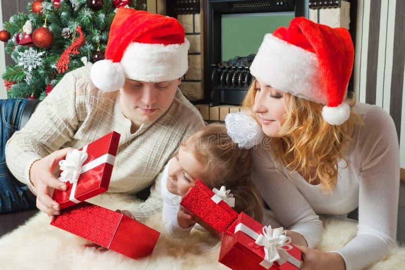 Dziewczyna z rodzicami patrzeje prezenta nearthe choinki obraz stock