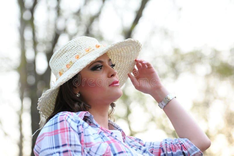 Dziewczyna z rozważnym spojrzeniem i kapelusz na jej głów pozach w parku zdjęcia royalty free
