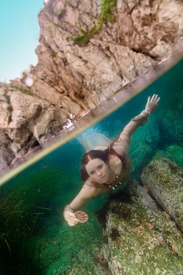 Dziewczyna z seashell podwodnym fotografia stock