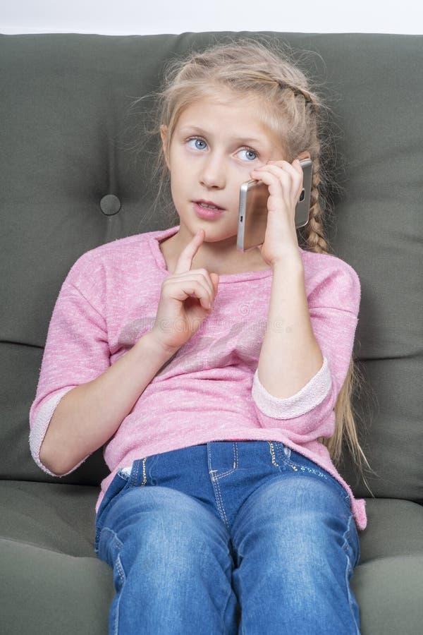 Dziewczyna z smartphone na leżance obrazy stock
