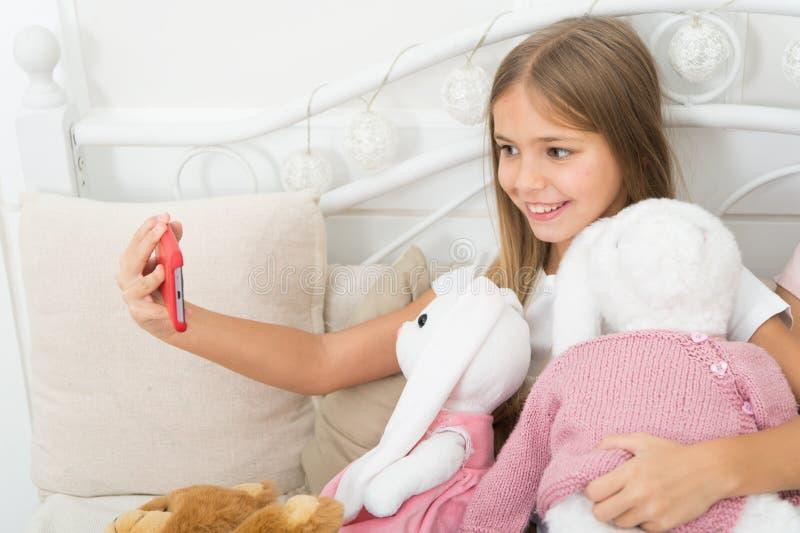 Dziewczyna z smartphone używa nowożytną technologię Selfie z faworyt zabawką Wysyła selfie fotografię twój przyjaciela socjalny s obraz royalty free