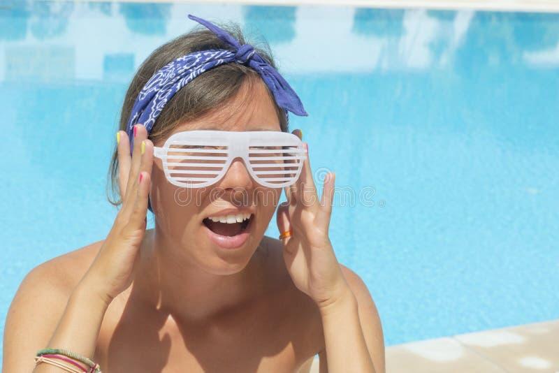 Dziewczyna z szalonymi okularami przeciwsłonecznymi pozuje basenem zdjęcia stock