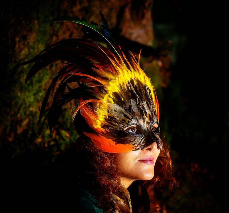 Dziewczyna z szamańską piórko maską i historyczna suknia w lasów otoczeniach obrazy royalty free