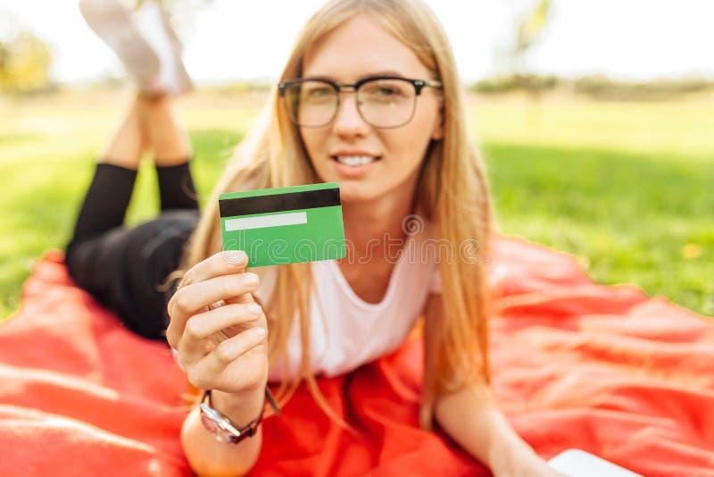 Dziewczyna z szkłami pokazuje kredytowej karty obsiadanie w parku na koc zdjęcie royalty free
