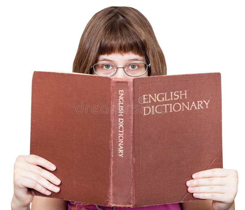 Dziewczyna z szkieł spojrzeniami nad Angielskim słownikiem zdjęcie royalty free