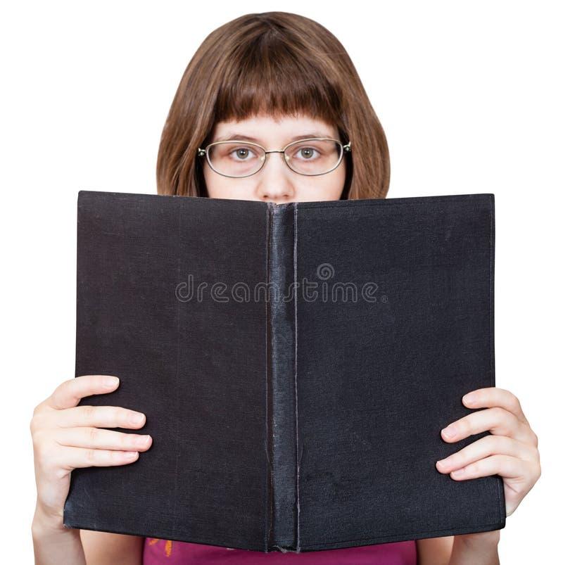 Dziewczyna z szkieł spojrzeniami nad dużą książką odizolowywającą zdjęcie stock