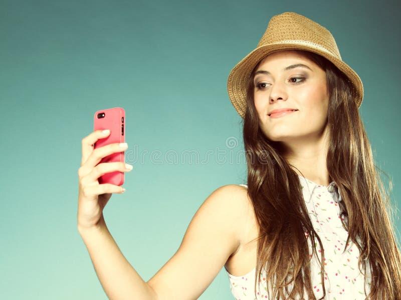 Dziewczyna z telefonem komórkowym bierze fotografię ona zdjęcia stock
