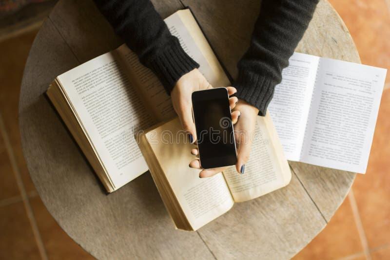 Dziewczyna z telefonem komórkowym i książkami na drewnianym stole zdjęcia stock