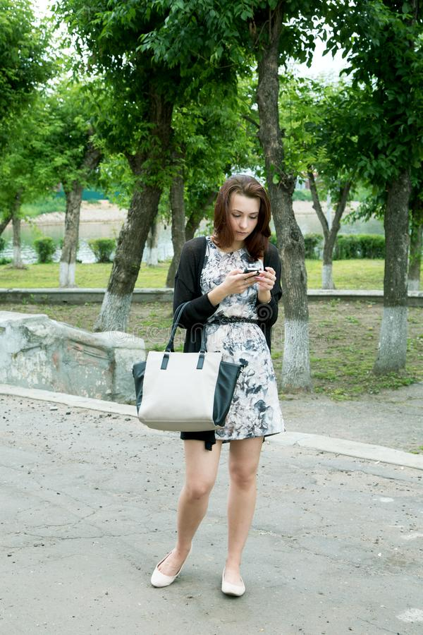 Dziewczyna z telefonem w ogródzie na rzece obrazy royalty free