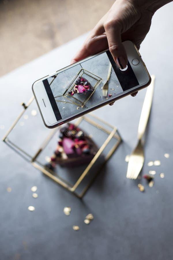 dziewczyna z telefonem w ręce bierze obrazek smakowity tort obraz stock