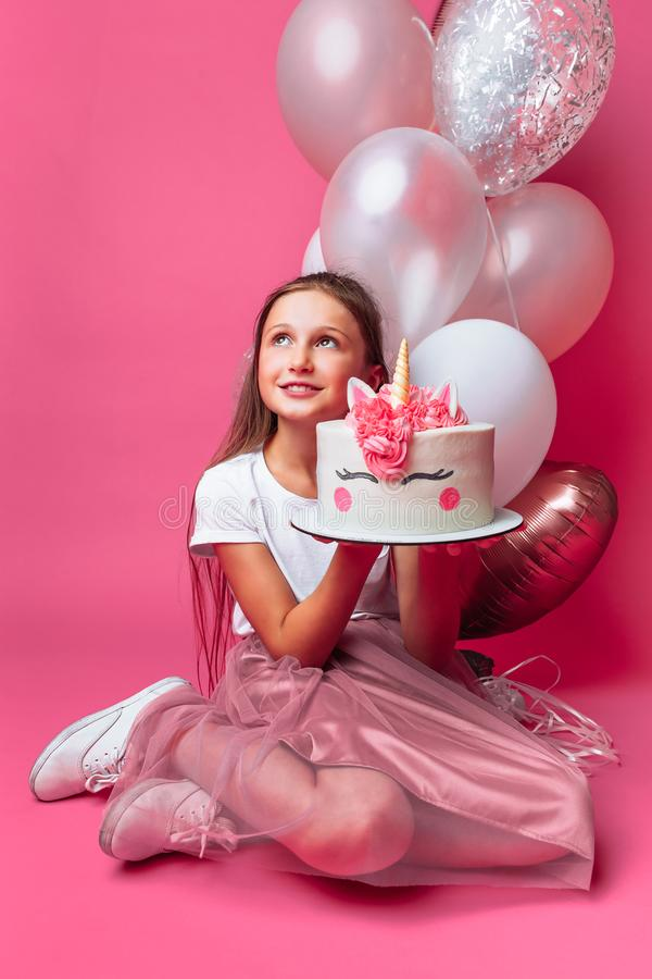 Dziewczyna z tortem dla urodziny w studiu na różowym tle, świąteczny nastrój w pełnym przyroscie w rękach projektanta tort, zdjęcia royalty free