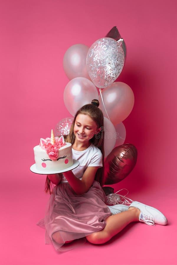 Dziewczyna z tortem dla urodziny w studiu na różowym tle, świąteczny nastrój w pełnym przyroscie w rękach projektanta tort, obrazy royalty free