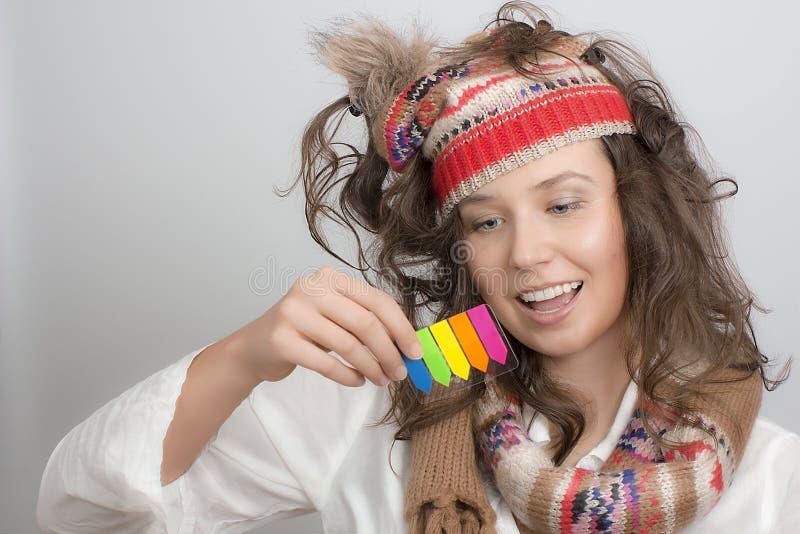 Dziewczyna z trykotowego kapeluszowego mienia kleistym nutowym strzałkowatym highlighter ta zdjęcia stock