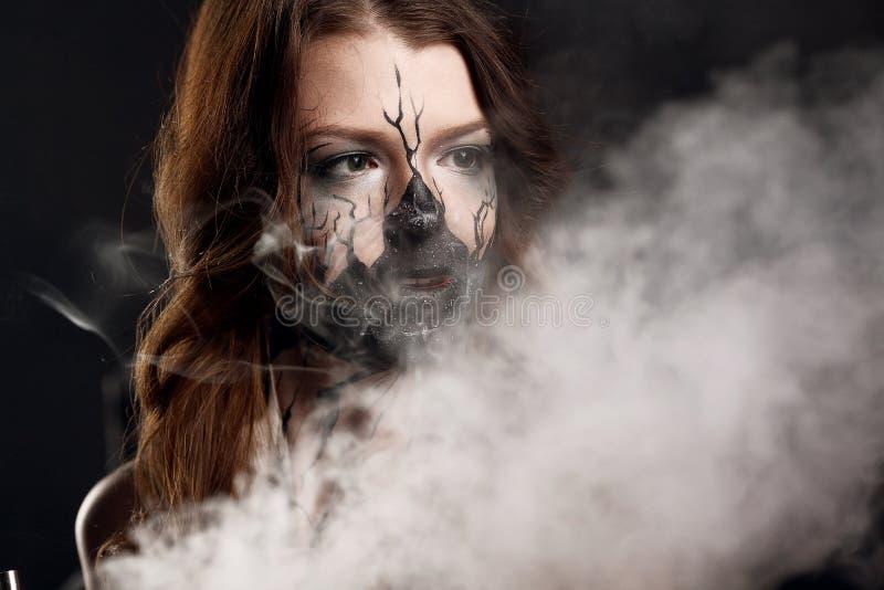 Dziewczyna z uzupełniał i elektroniczny papieros robi chmurom fotografia stock