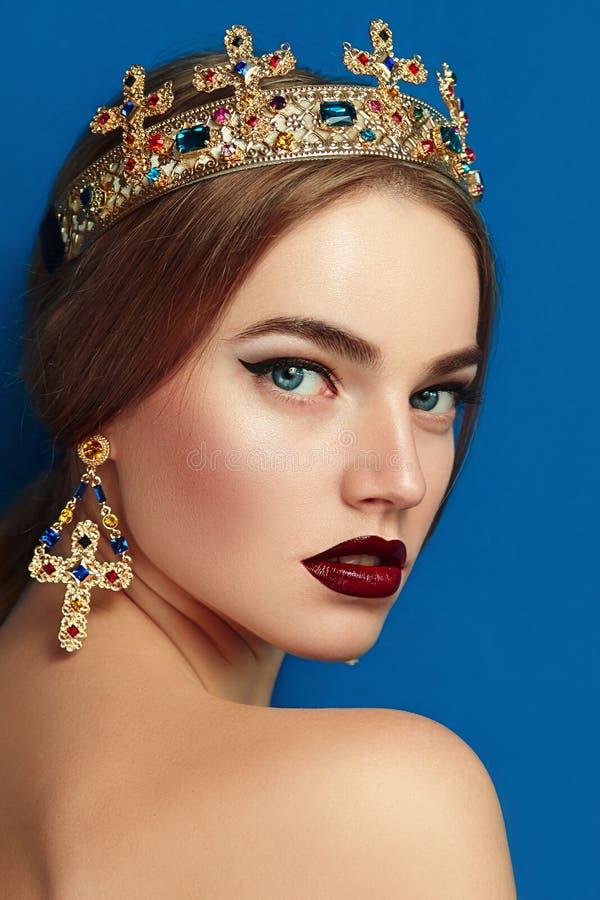 Dziewczyna z złotą koroną złotymi kolczykami i zdjęcie stock