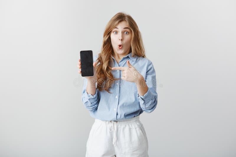 Dziewczyna zadziwiająca z nowym telefonem Portret zafascynowana szokująca młoda europejska kobieta z blondynem w bluzka seansie obrazy stock