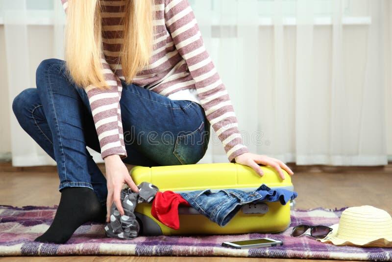 Dziewczyna zamyka walizkę obrazy stock