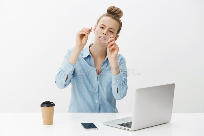 Dziewczyna zdejmuje szkła sprawdza obiektyw i whiping brud jako obsiadanie zanudzał w biurowy pobliski laptopu i smartphone pić zdjęcie stock
