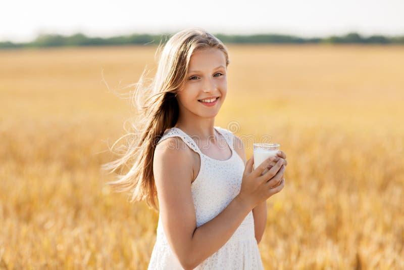 Dziewczyna ze szklanką mleka na polu zbóż fotografia stock