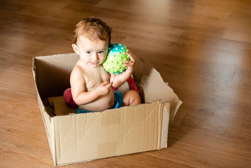 Dziewczynka bawiąca się kulą w pudełku z tektury i robiąca uroczą twarz obraz stock