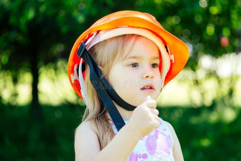 Dziewczynka budująca kask na tle zielonego parku obraz stock